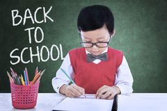 Cute child back to school and drawing in class. Male elementary school student back to school and drawing in the classroom while wearing uniform Royalty Free Stock Photos
