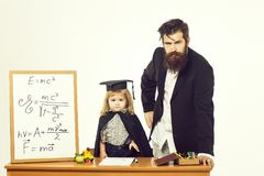 Cute child and bearded professor. Cute boy little child in squared hat and black academic gown sitting at desk near school blackboard with formulas and professor royalty free stock images