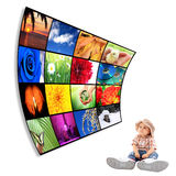 Cute child with big Tv. Baby watching big panel of TV, HD, movie Royalty Free Stock Photography