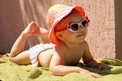 Cute child in bikini and sunglasses lying on a green towel relaxing. clouse-up portrait. summer Stock Photo