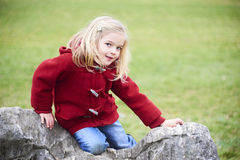 A cute child blond girl posing on a rock outside. A cute five year old blond girl posing on a rock outside, spring, park Royalty Free Stock Photo