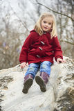 A cute child blond girl posing on a rock outside. A cute child old blond girl posing on a rock outside, spring, park Royalty Free Stock Image