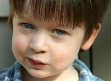 Cute child with blue eyes, close-up. Cute child with blue eyes and matching blue shirt, close-up, and looking mischievous Royalty Free Stock Photos