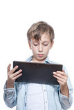 Cute child in blue shirt holding a tablet computer Royalty Free Stock Image