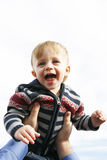Cute child boy. Happy laughing cute child toddler boy being held up in air by dad Stock Photography