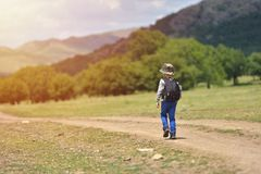Cute child boy with backpack walking on a little path in mountains. Hiking kid Royalty Free Stock Images