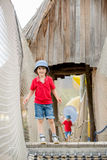 Cute child, boy, climbing in a rope playground structure Stock Photos
