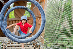 Cute child, boy, climbing in a rope playground structure Stock Image