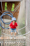 Cute child, boy, climbing in a rope playground structure Stock Images