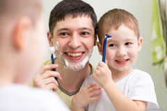 Cute child boy and daddy shave looking at mirror Royalty Free Stock Images