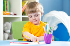 Cute child boy is drawing with color pencils in nursery royalty free stock image