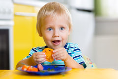 Cute child boy eats healthy food vegetables. Cute child little boy eats healthy food vegetables stock image