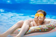 Cute child boy on funny inflatable donut float ring in swimming pool with oranges. Teenager learning to swim stock images