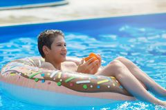 Cute child boy on funny inflatable donut float ring in swimming pool with oranges. Teenager learning to swim, have fun in outdoor stock photo