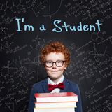 Cute child boy with ginger hair holding books in classroom on chalkboard background. Back to school concept.  royalty free stock photo