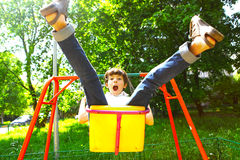 Cute child, boy, having fun on a swing. In the backyard on sunset stock images
