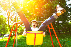 Cute child, boy, having fun on a swing. In the backyard on sunset royalty free stock photo