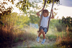 Cute child, boy, having fun on a swing in the backyard. On sunset royalty free stock photos