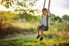Cute child, boy, having fun on a swing in the backyard. On sunset stock photo