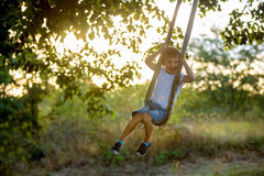 Cute child, boy, having fun on a swing in the backyard. On sunset royalty free stock images