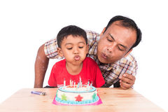 Cute child boy with his father blowing birthday cake royalty free stock photo