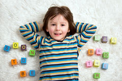 Cute child, boy, play with toy blocks, lying on the floor Stock Image