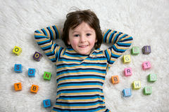 Cute child, boy, play with toy blocks, lying on the floor Royalty Free Stock Images