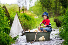 Cute child, boy, playing with boat and ducks on a little rive. R, sailing and boathing. Kid having fun, childhood happiness concept stock photography