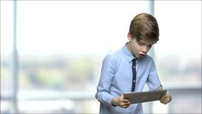 Cute child boy playing game on digital tablet. stock footage