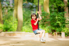 Cute child, boy, rides on Flying Fox play equipment in a childre Royalty Free Stock Images