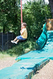Cute child, boy, rides on Flying Fox play equipment in a childre Royalty Free Stock Photo