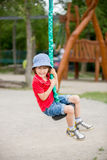 Cute child, boy, rides on Flying Fox play equipment in a childre Stock Photography