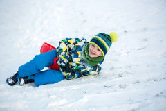 Cute child, boy, sliding with bob in the snow, wintertime Royalty Free Stock Image