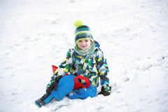 Cute child, boy, sliding with bob in the snow, wintertime Stock Photos