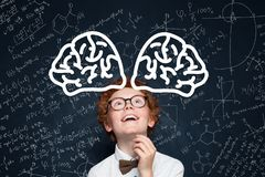Cute child boy student in glasses having fun against blackboard background with science formulas.  stock images