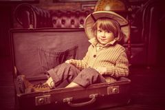 Child playing at home. Cute child boy in a travel suitcase playing at home. Childhood. Fantasy, imagination stock photos
