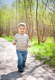 Cute child boy walking on road Stock Photography