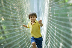 Cute child, boy, walking in a rope playground structure, Royalty Free Stock Photos