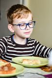 Cute child at breakfast. Cute  preschool child  with a readingglasses at home  at breakfast in the morning Royalty Free Stock Photos