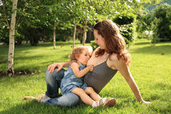 Cute child breastfeeding. Cute woman nurses her little child in park. Shallow depth of field Stock Image