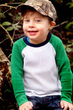 Cute Child with Camo Cap. A closeup of an adorable 4 year old boy child with a missing tooth, wearing a camo bill cap. Shallow depth of field Royalty Free Stock Photos
