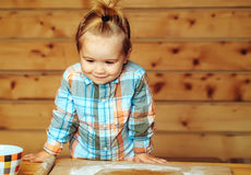 Cute child in checkered shirt cooking with dough and flour. Adorable small child chef or cute baby boy with smiling face in fashionable chekered shirt cooking on Royalty Free Stock Photos