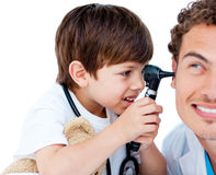 Cute child checking doctor's ears Stock Photos