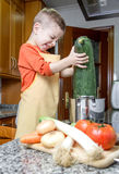 Cute child chef cooking big zucchini in a pot Stock Image