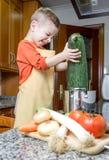 Cute child chef cooking big zucchini in a pot stock image