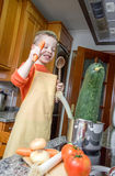 Cute child chef cooking big zucchini in a pot Stock Photos