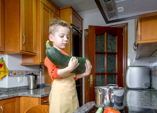 Cute child chef cooking big zucchini in a pot royalty free stock photo