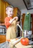 Cute child chef cooking big zucchini in a pot Royalty Free Stock Photos