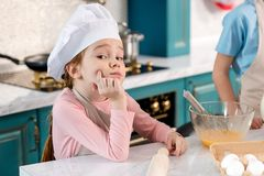 cute child in chef hat and apron sitting with hand on chin and looking at camera stock photos