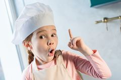 Cute child in chef hat pointing up with finger and looking at camera. In kitchen Royalty Free Stock Photography